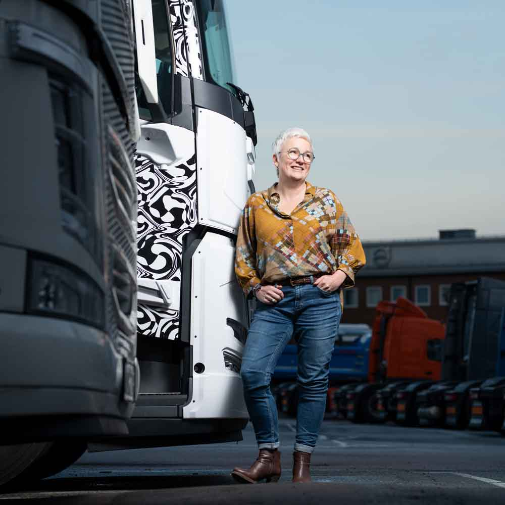 Carina Byström leans against the cab exterior of the Volvo FM