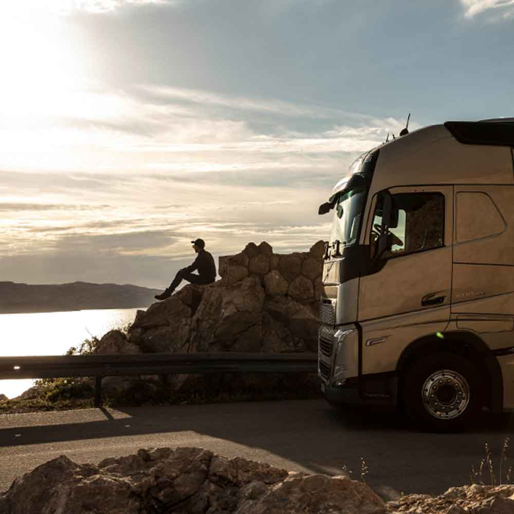 A driver sits on a rock looking out to sea at sunset, with his Volvo FH truck parked beside him