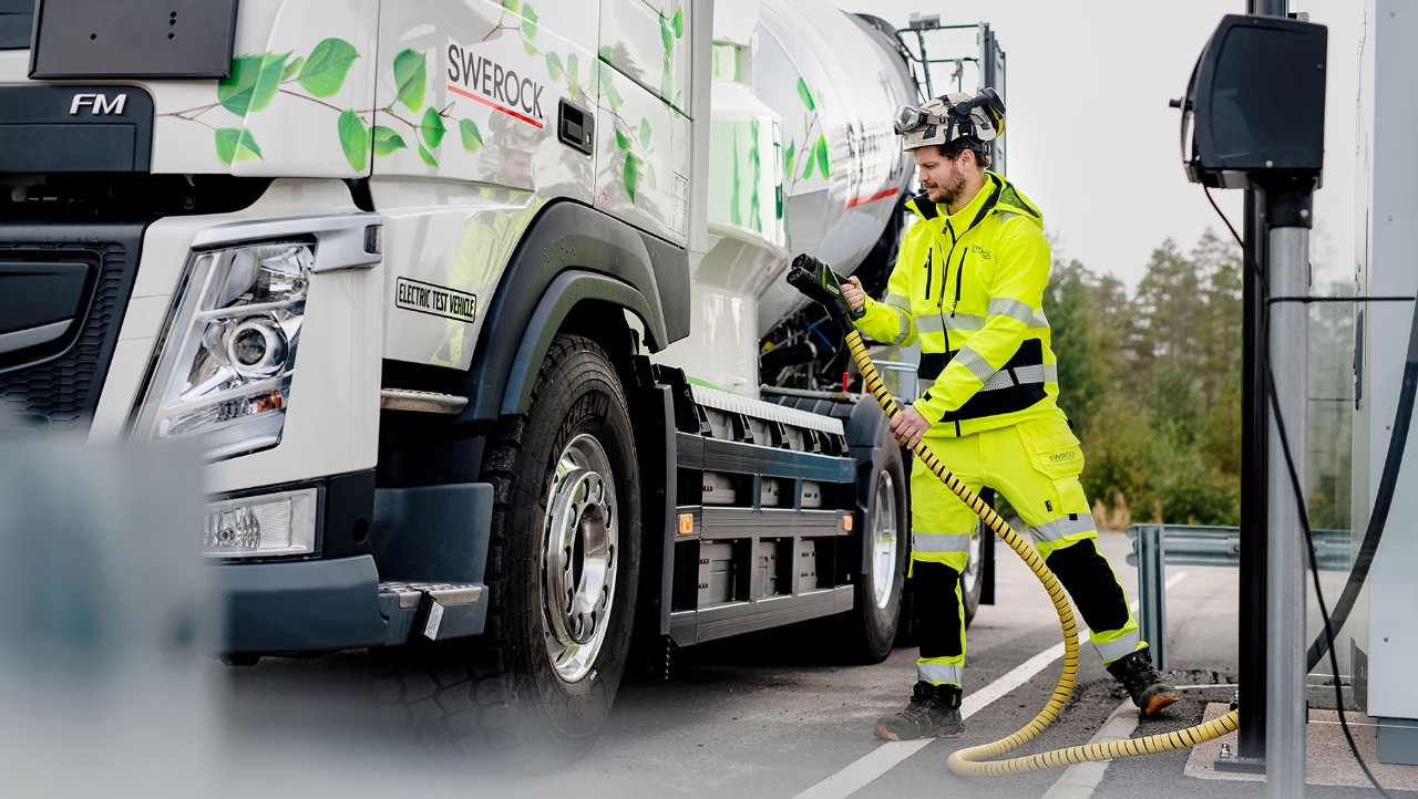 A man in high visibility clothing carries a charging cable to the Volvo FM electric truck