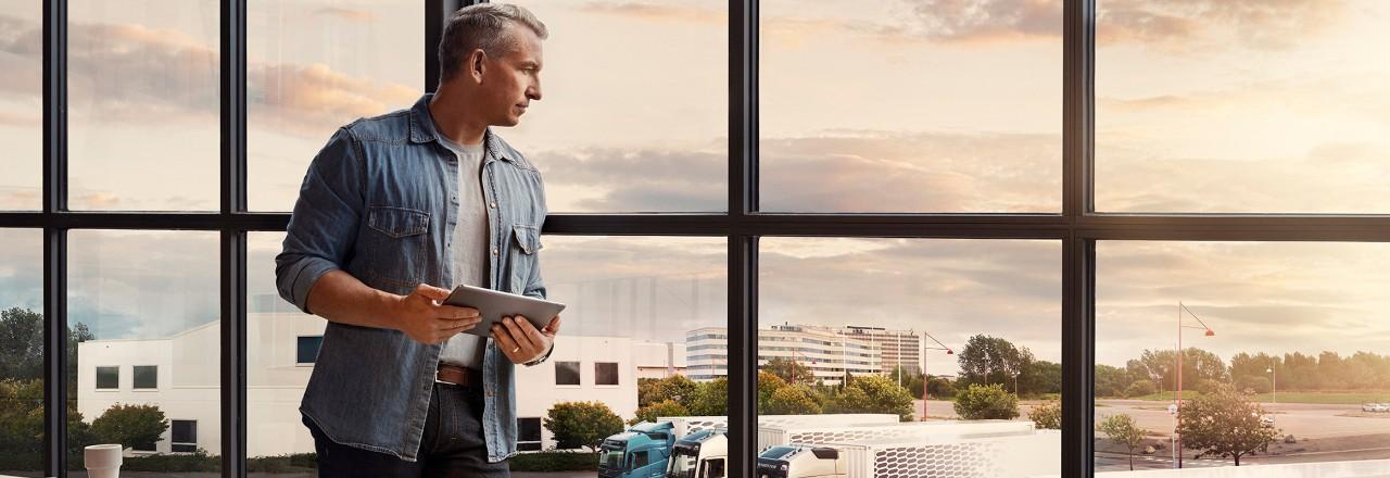 Un hombre que sostiene una tableta está junto a una ventana y mira hacia abajo su flota de camiones